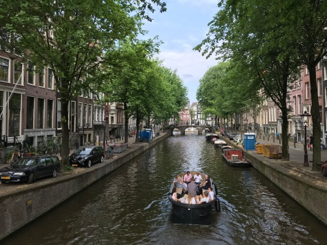 Boat going down a canal in Amsterdam